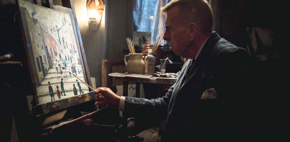 Artist LS Lowry painting in a dark room