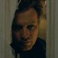 A man looks through a crack in a door